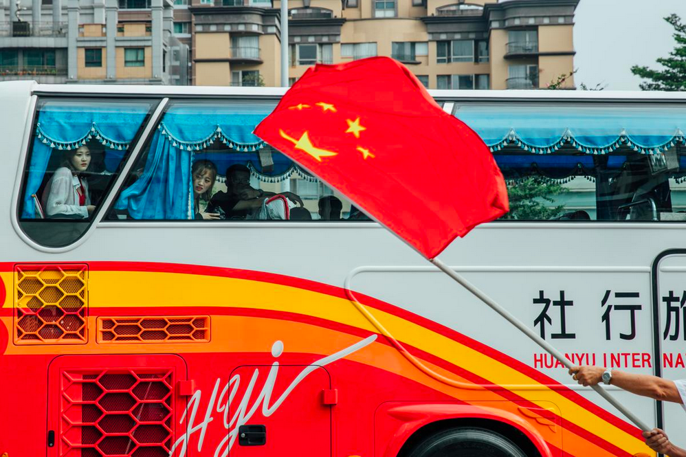 An Association member waves the PRC canton in front of a charter tour bus. Yu Chih-wei/The Reporter.