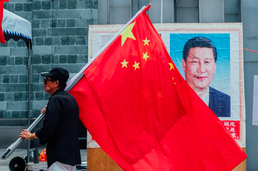 Association Vice-President Li You-ming walks in front of a portrait of Xi Jinping. Yu Chih-wei/The Reporter.