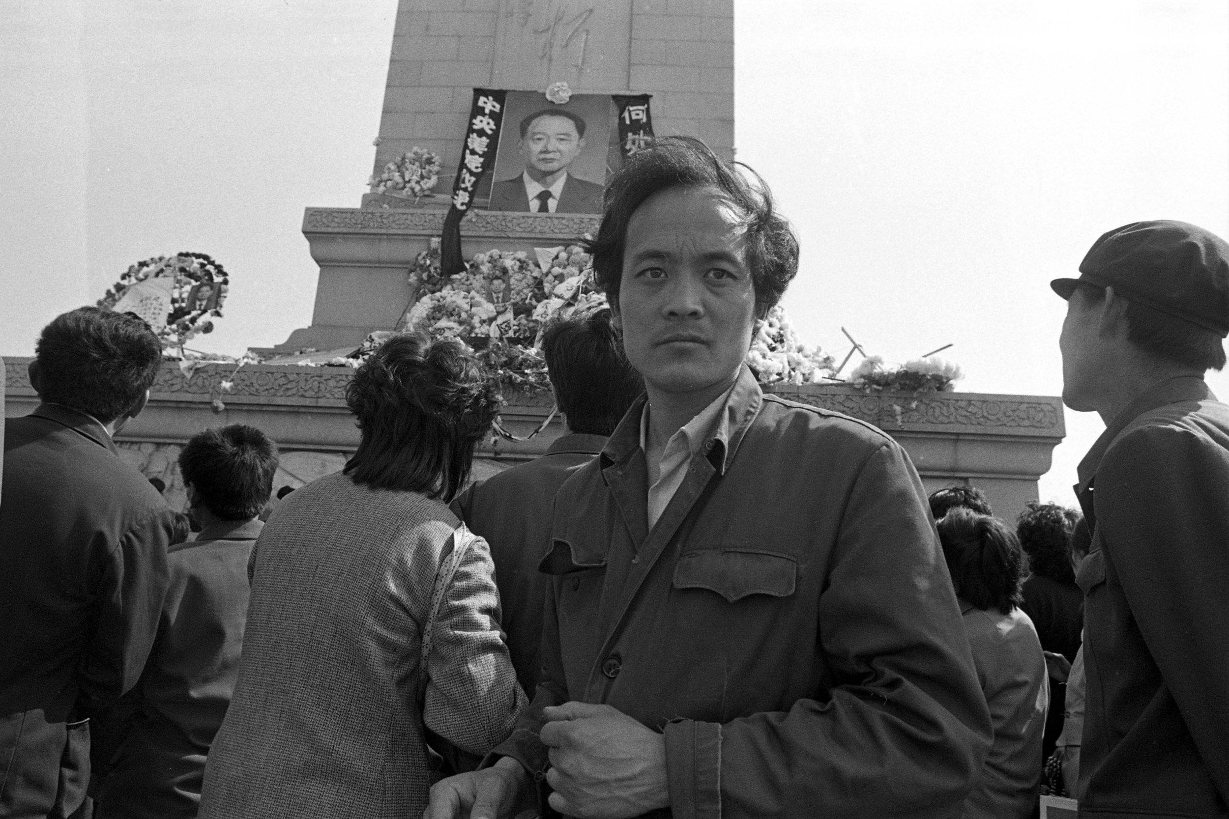A young man looks on with a photo of former CCP general-secretary Hu Yaobang leaning against the Monument to the People's Heroes in the background. Photo taken on April 25, 1989. Photo credit: Hsieh San-tai, Howling 1989.