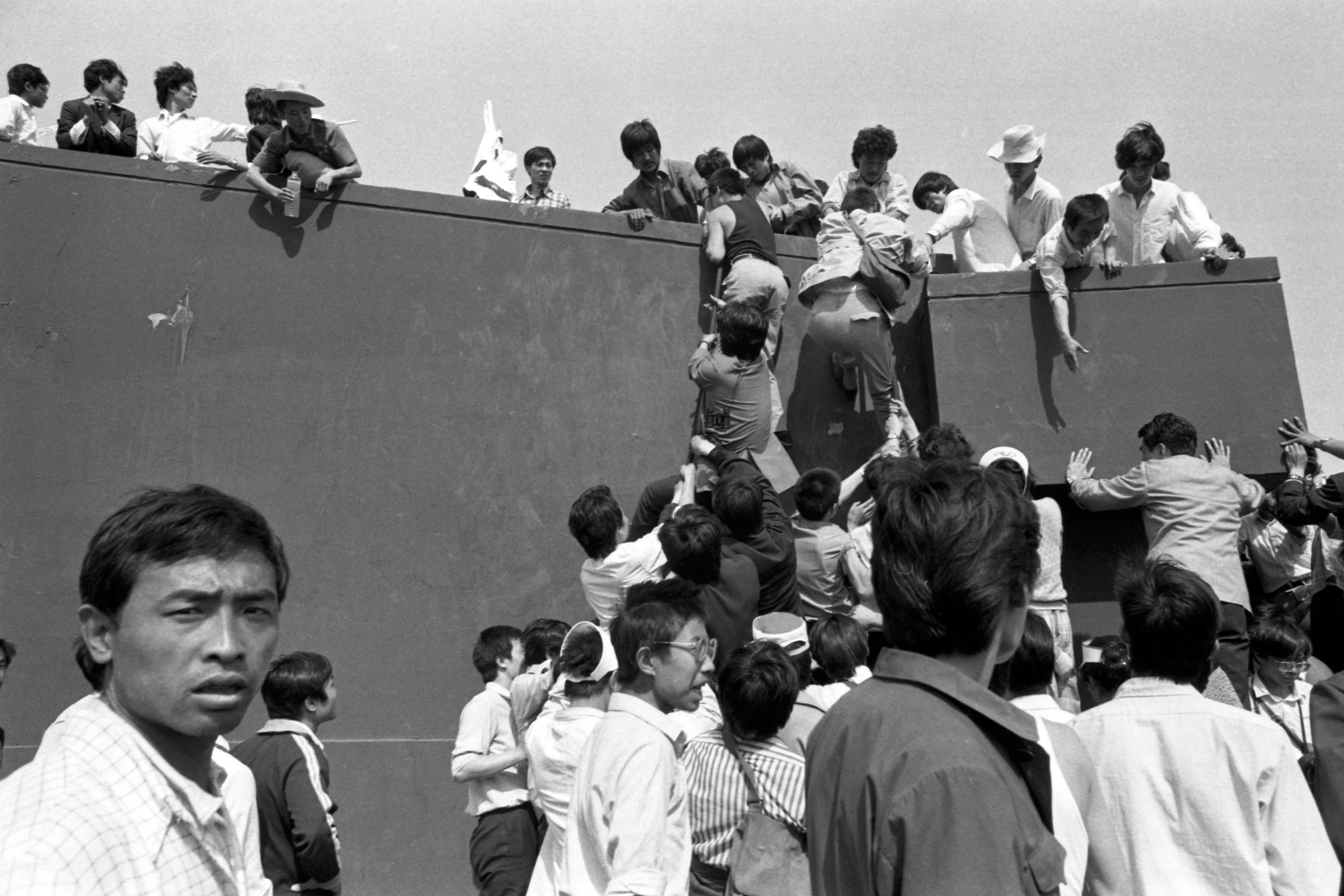 Protesters climb up the wall in Tiananmen Square. Photo taken on May 17, 1989. Photo credit: Hsieh San-tai, Howling 1989.