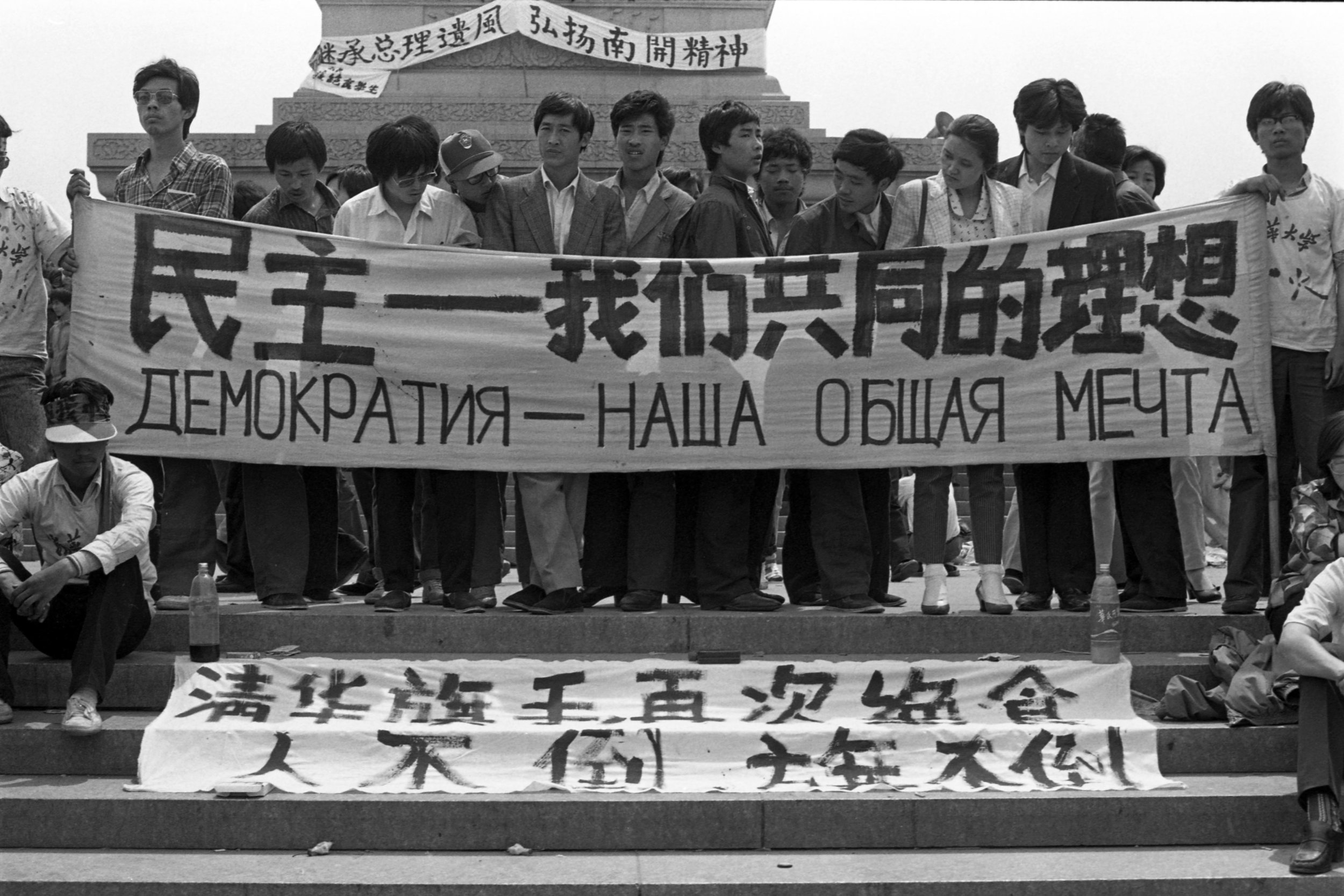 "Protesters in front of the Monument to the People's Heroes hold a banner reading ""Democracy is our shared aspiration"" in Simplified Chinese and Russian. Timed to coincide with Mikhail Gorbachev's visit to Beijing in mid-May. Photo taken on May 16, 1989. Photo credit: Hsieh San-tai, Howling 1989."