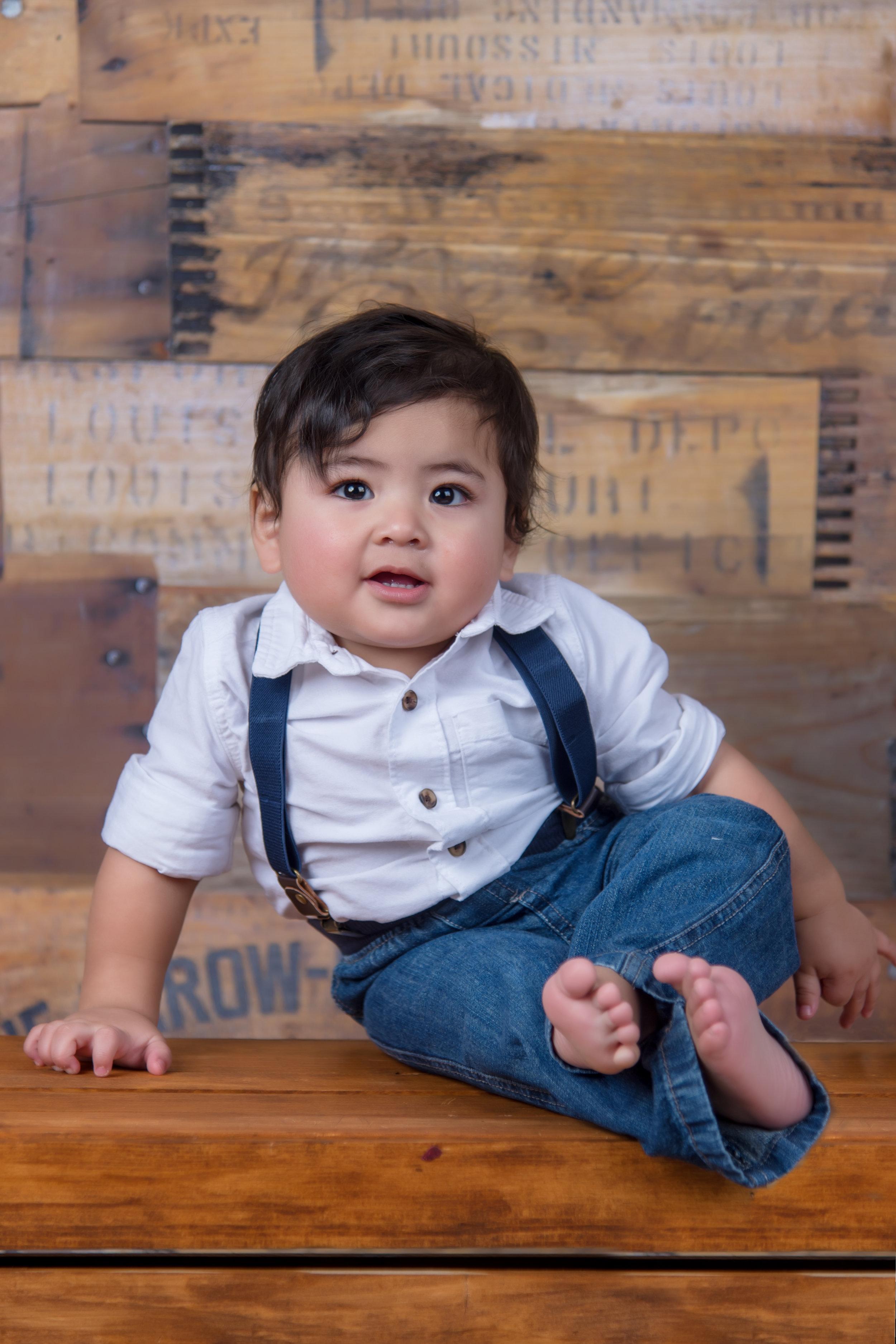 1st birthday portrait little boy in suspenders on crate wood
