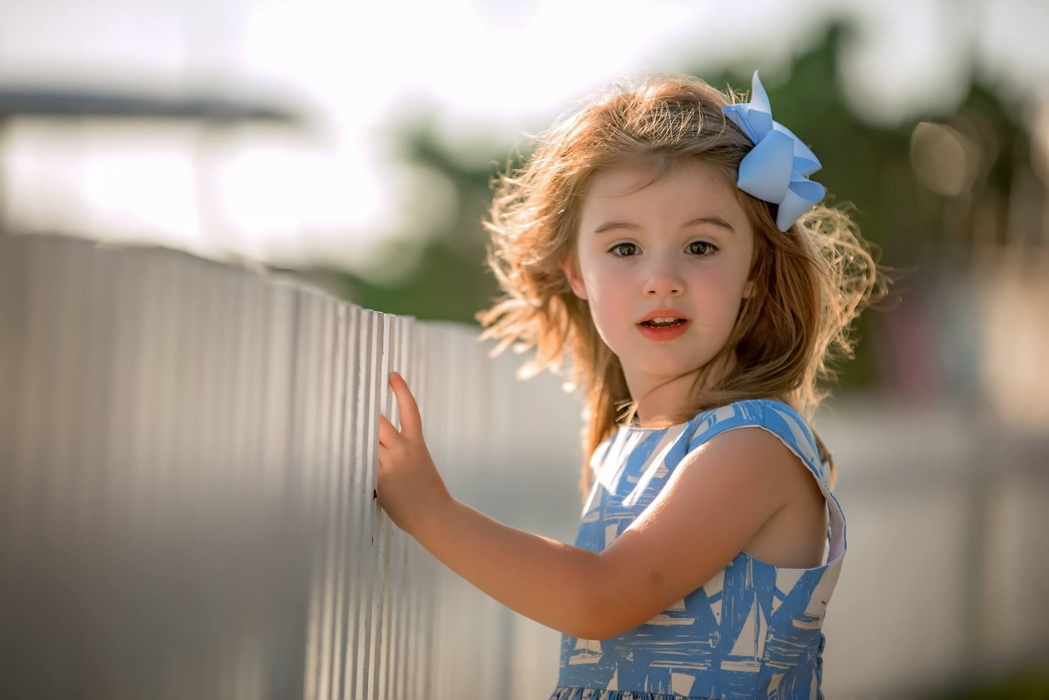 girl with wind blown hair in baby blue sail boat dress against fence at ocracoke island in north carolina