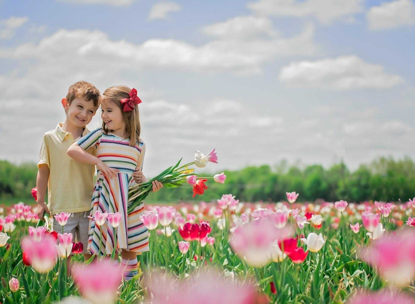 boy girl twins in tulip garden spring portrait