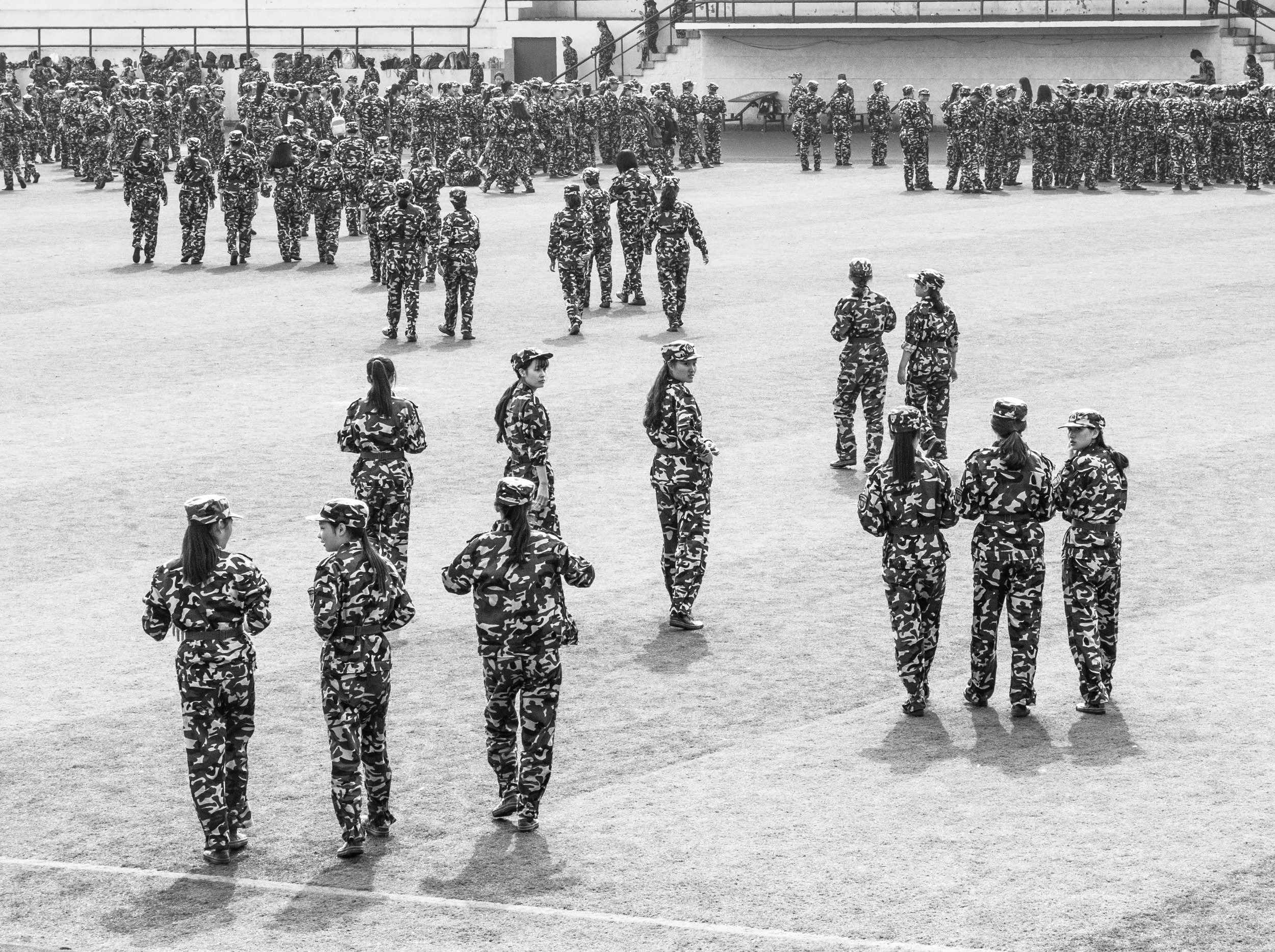 Xiangdao, China, 2014. © PMB No idea what these young women were doing - it looked like a college cadet force - they went on to practise unarmed combat and bandage imaginary wounds. Categories? Military; patterns; uniformity; people in action; black and white?