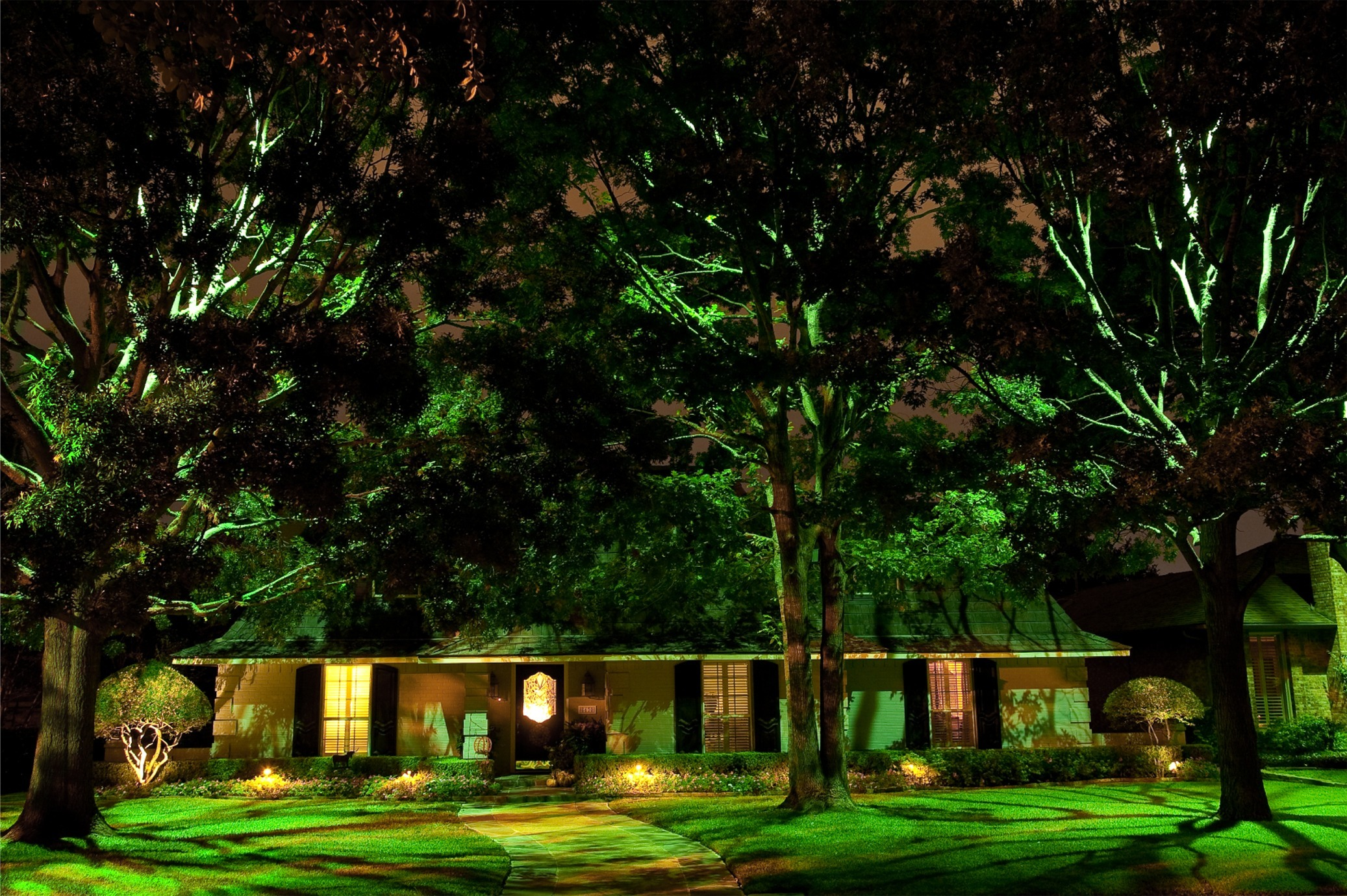 Create moonlighting techniques by placing a large fixture with a full glare guard high up inside a tree, and angled downwards. This effect looks like moonlight shining down through the branches. It causes attractive shadow patterns on the ground to appear, plus it provides a very natural and beautiful lighting effect.