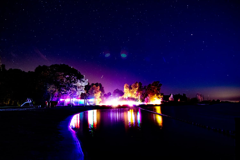 Festivalterrein in het donker, gezien vanaf het water
