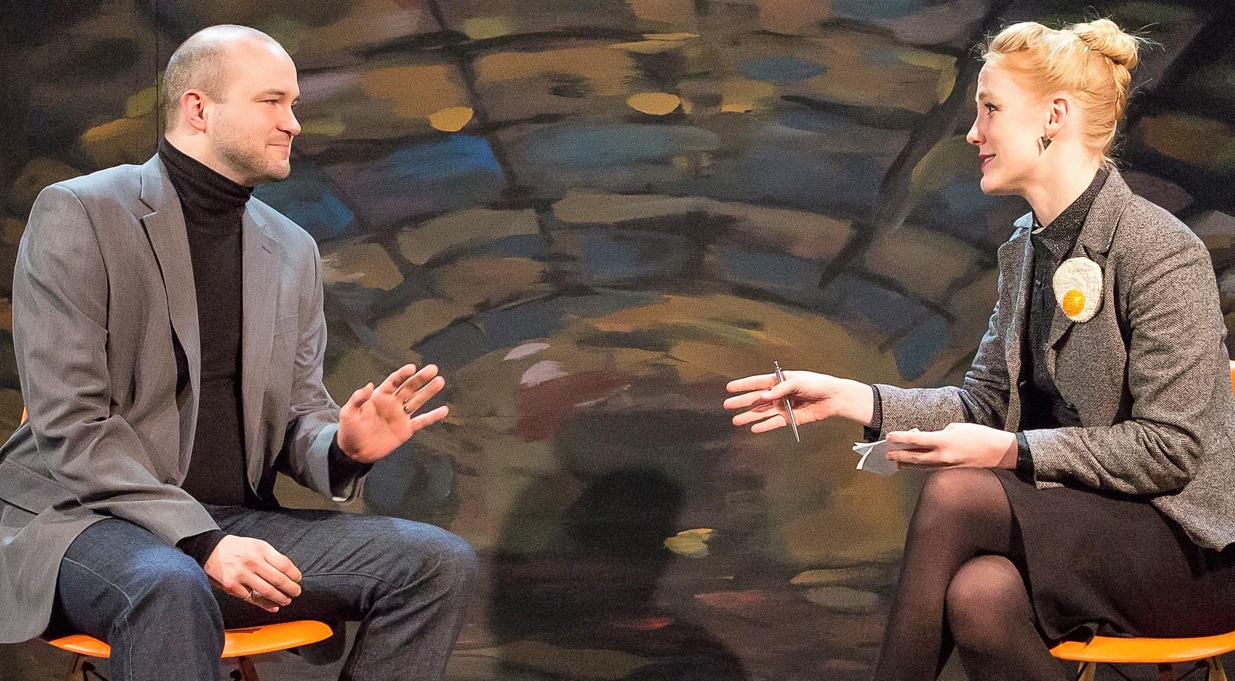Seymour as Jonathan is interviewed by Grete, a German journalist (Ally Carey).