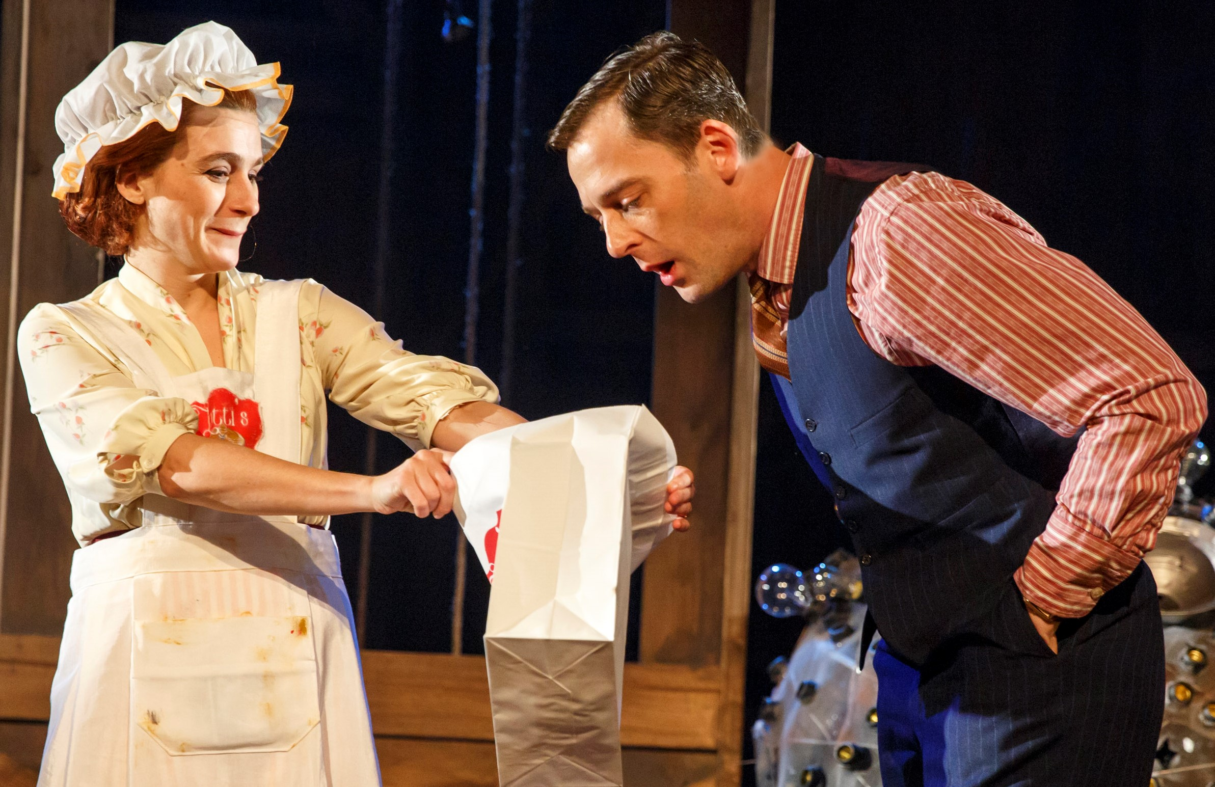Ruth (Aya Cash) shows her husband Lou (Ken Barnett) pancakes she has brought home from the 1933 world's fair, in the Debate Society's  The Light Years . Top, from left: Rocco Sisto as Steele MacKaye, Cash as Adeline, and Erik Lochtefeld as Hillary, with the Mooncart.