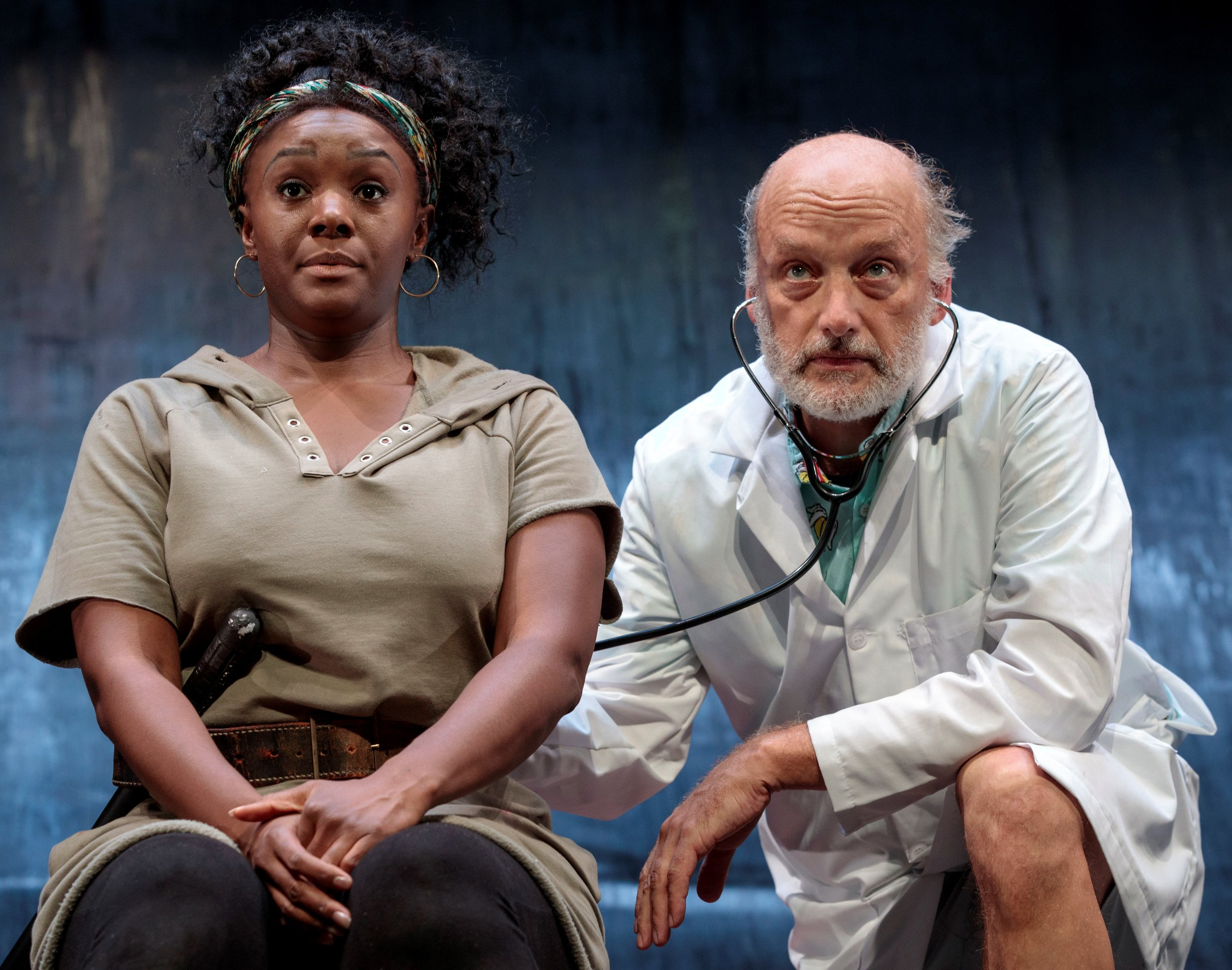 """Hester (Saycon Sengbloh) gets a checkup from the Doctor (Frank Wood). Top: Sengbloh surrounded by her """"five treasures"""" (from left): Ana Reeder, Russell G. Jones, Wood, Jocelyn Bioh and Michael Braun."""