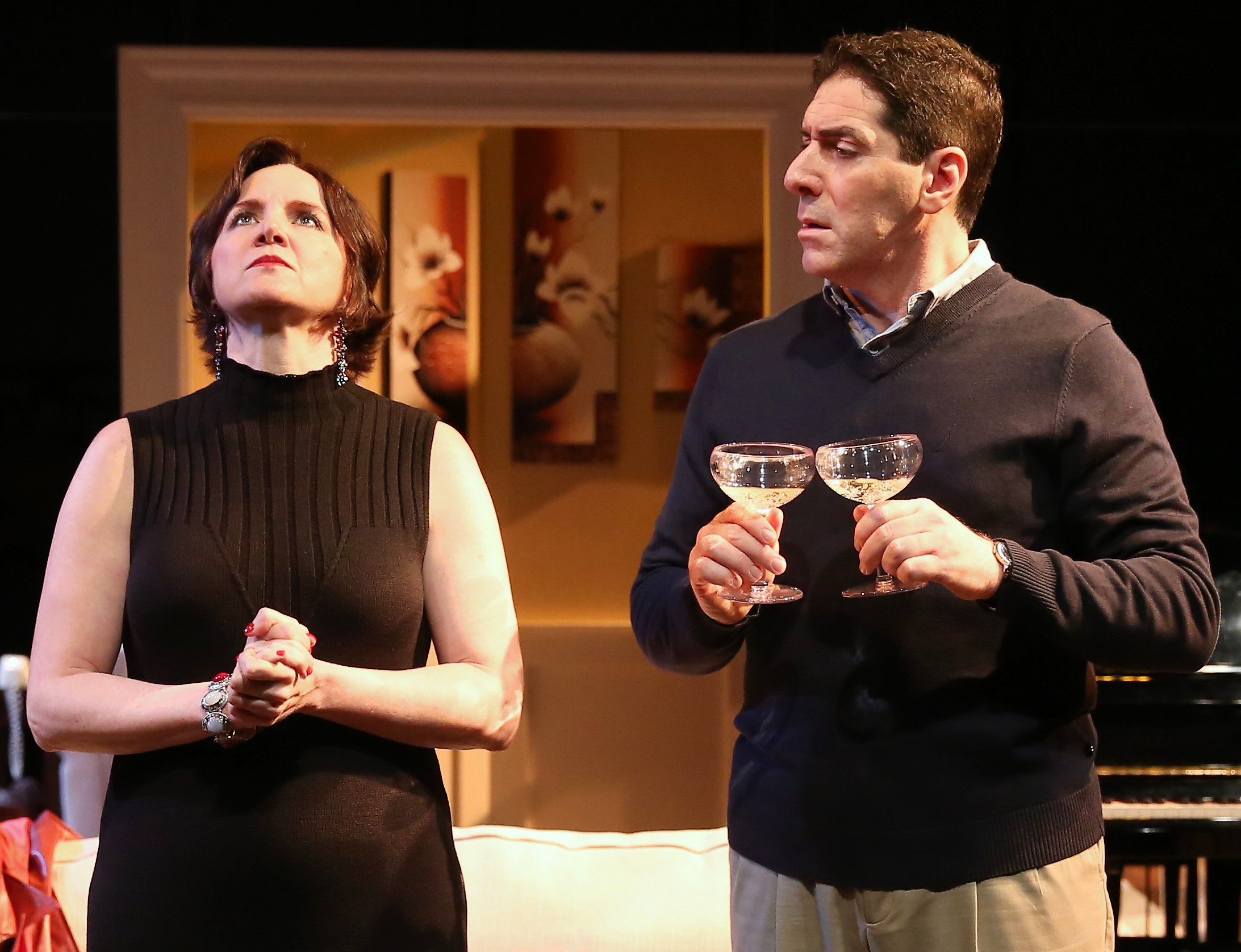 Julia (Pamela Sabaugh) is perplexed by a blank wall in the suburban living room of Roger (played by Nicholas Viselli) in the Theater Breaking Through Barriers production of A.R. Gurney's  The Fourth Wall . Top: Stephen Drabicki as Floyd (also reflected in the mirrored wall at the rear of the stage) with Sabaugh. Photographs by Carol Rosegg.