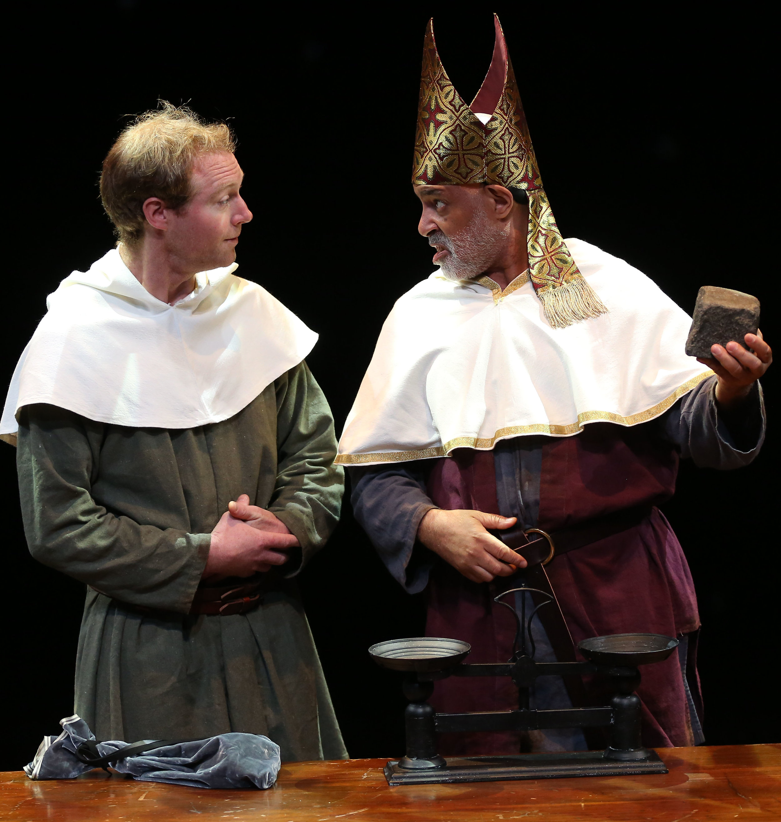 """Thomas Sommo and Michael Genet weigh the stones of the """"miracle"""" that Margery survives. Photographs by Carol Rosegg."""