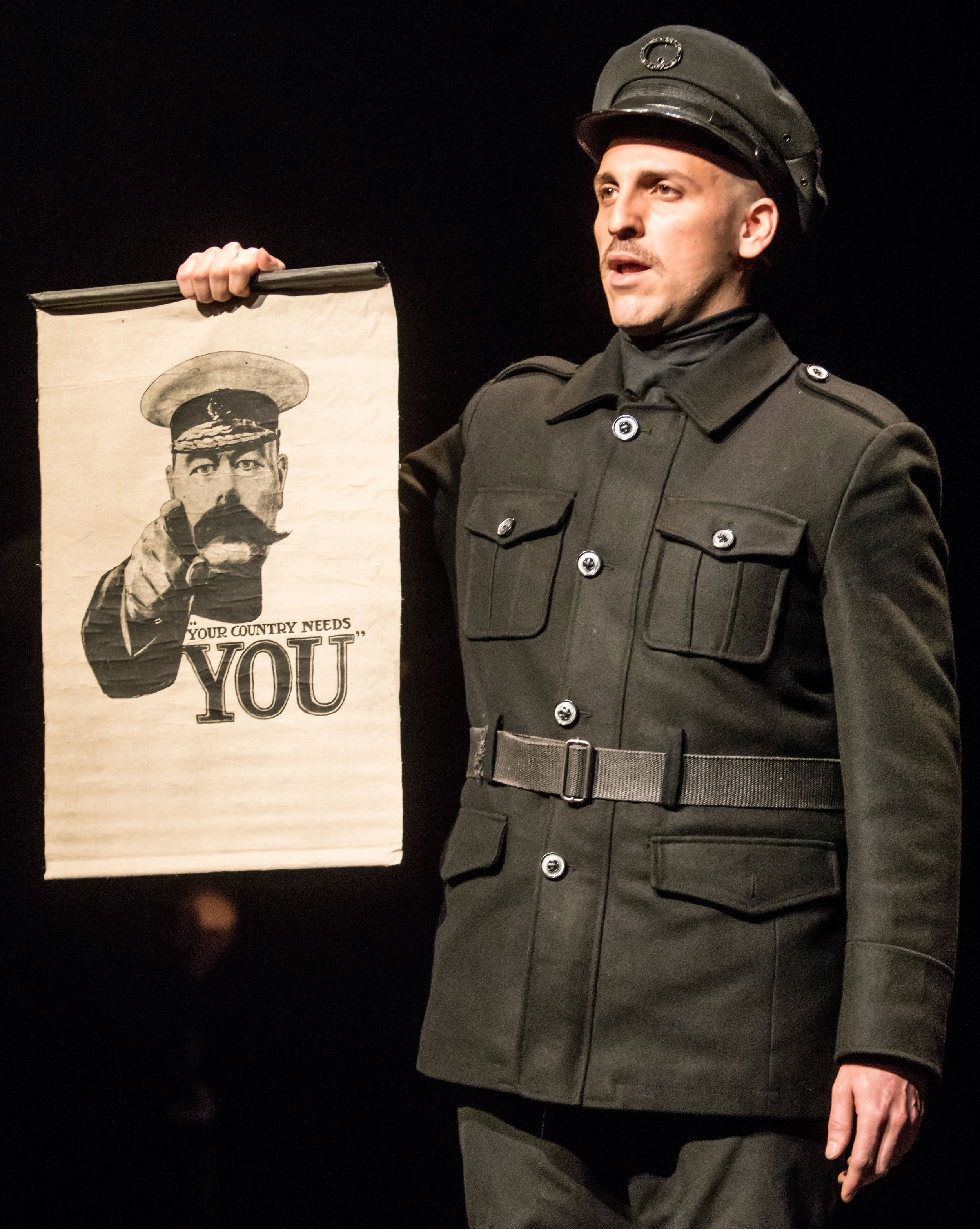 Rodolfo Nieto holds a World War I propaganda poster with the image of King George V in  All Is Calm: The Christmas Truce of 1914 . Top: Benjamin Dutcher in the role of a German soldier.