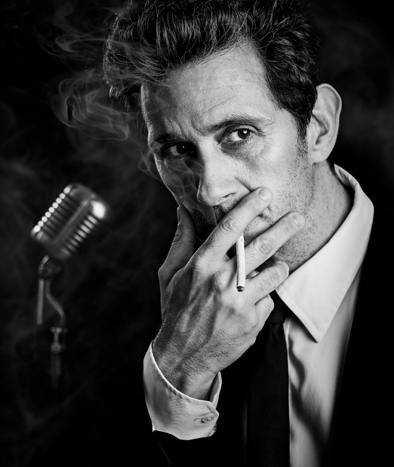 Ronnie Marmo as Lenny Bruce in a classic Bruce moment: at a microphone with a cigarette. Top: Marmo brings to life Bruce, the controversial stand-up comedian popular in the 1950s and '60s.