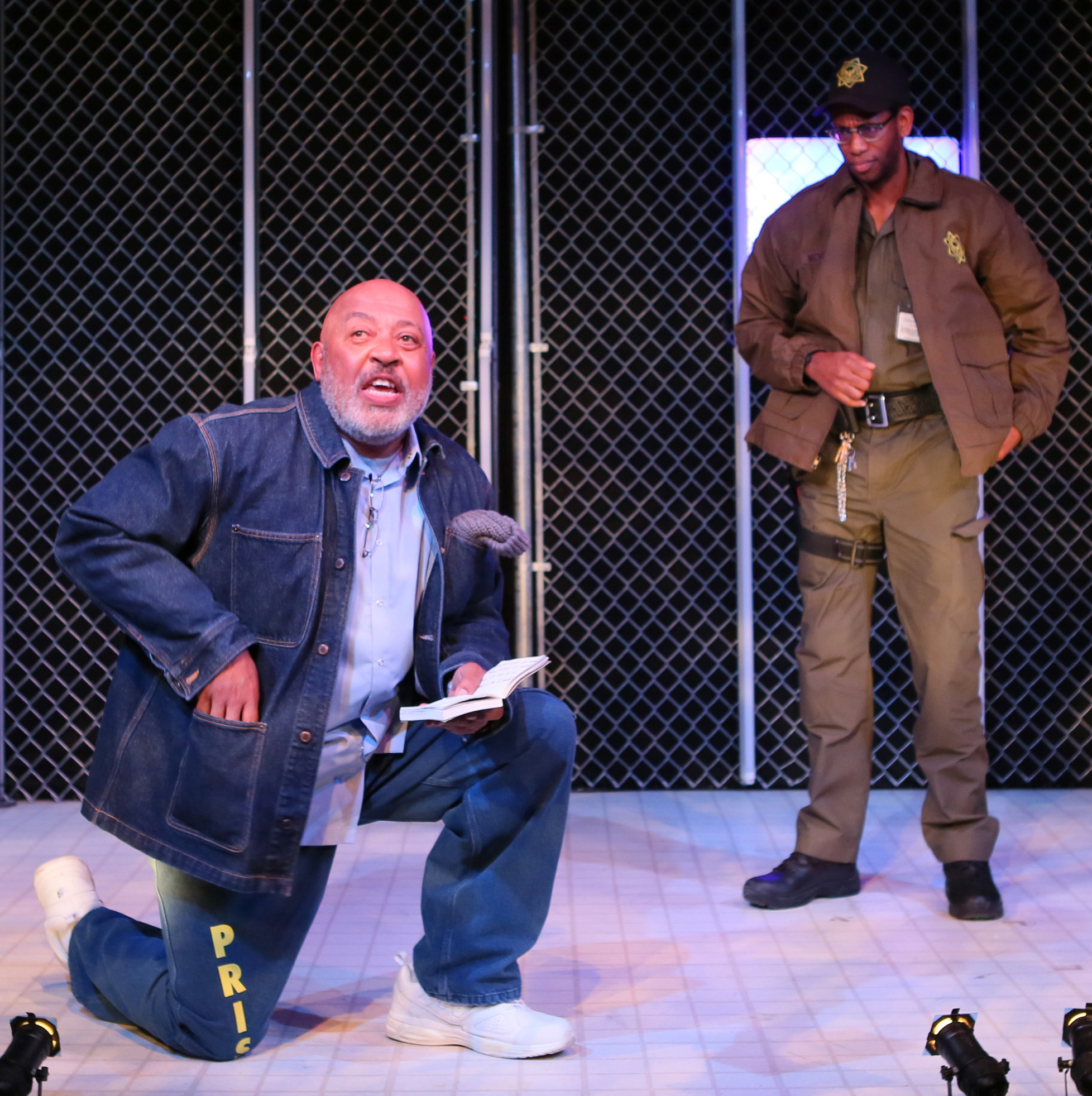 Keith Randolph Smith's Wise (left) submits to the extreme security measures of Eric Berryman's commanding officer, in  Lockdown . Top: Smith and Berryman with Zenzi Williams as Ernie.