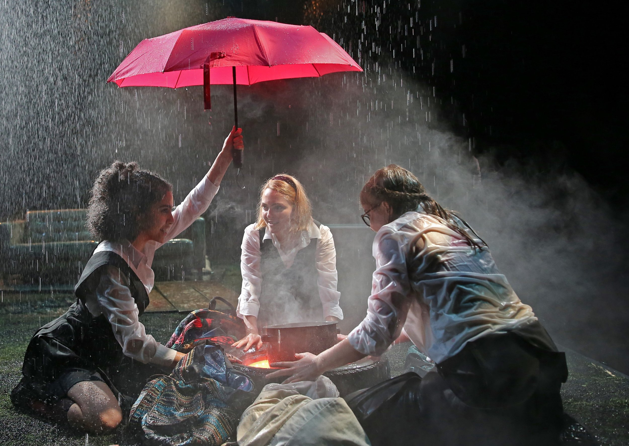 The witches (from left: Sharlene Cruz, Annasophia Robb, and Sophie Kelly-Hedrick ) cluster around their cauldron in Red Bull Theater's Mac Beth. Top: Isabelle Fuhrman (left) as Macbeth and Ayana Workman as Banquo.