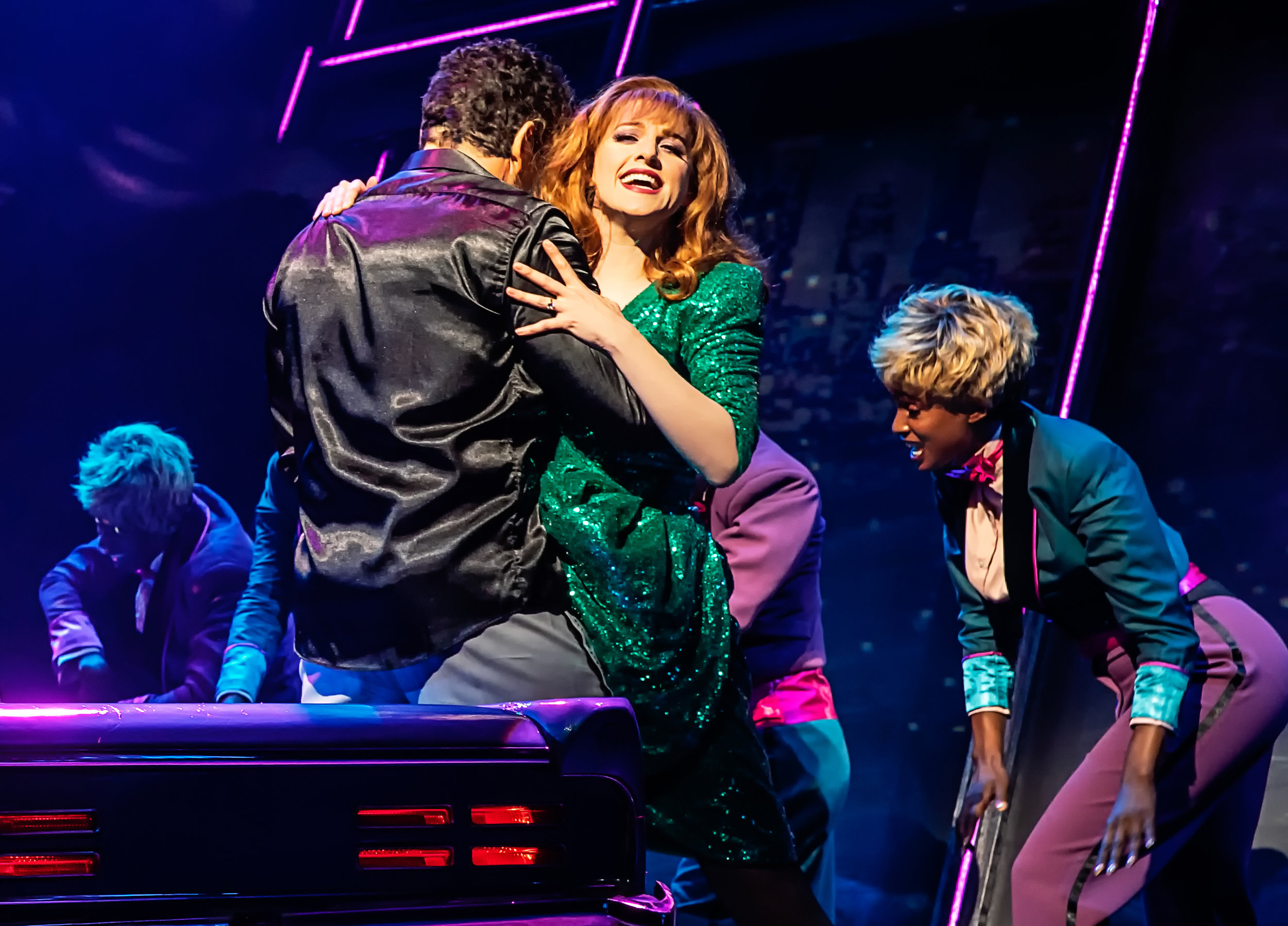 """From left: Falco (Bradley Dean) and his wife,. Sloane (Lena Hall), have a hot moment in a car, as Scherzzo (Harper Miles) does a backup dance to the Meat Loaf classic """"Paradise by the Dashboard Light."""""""
