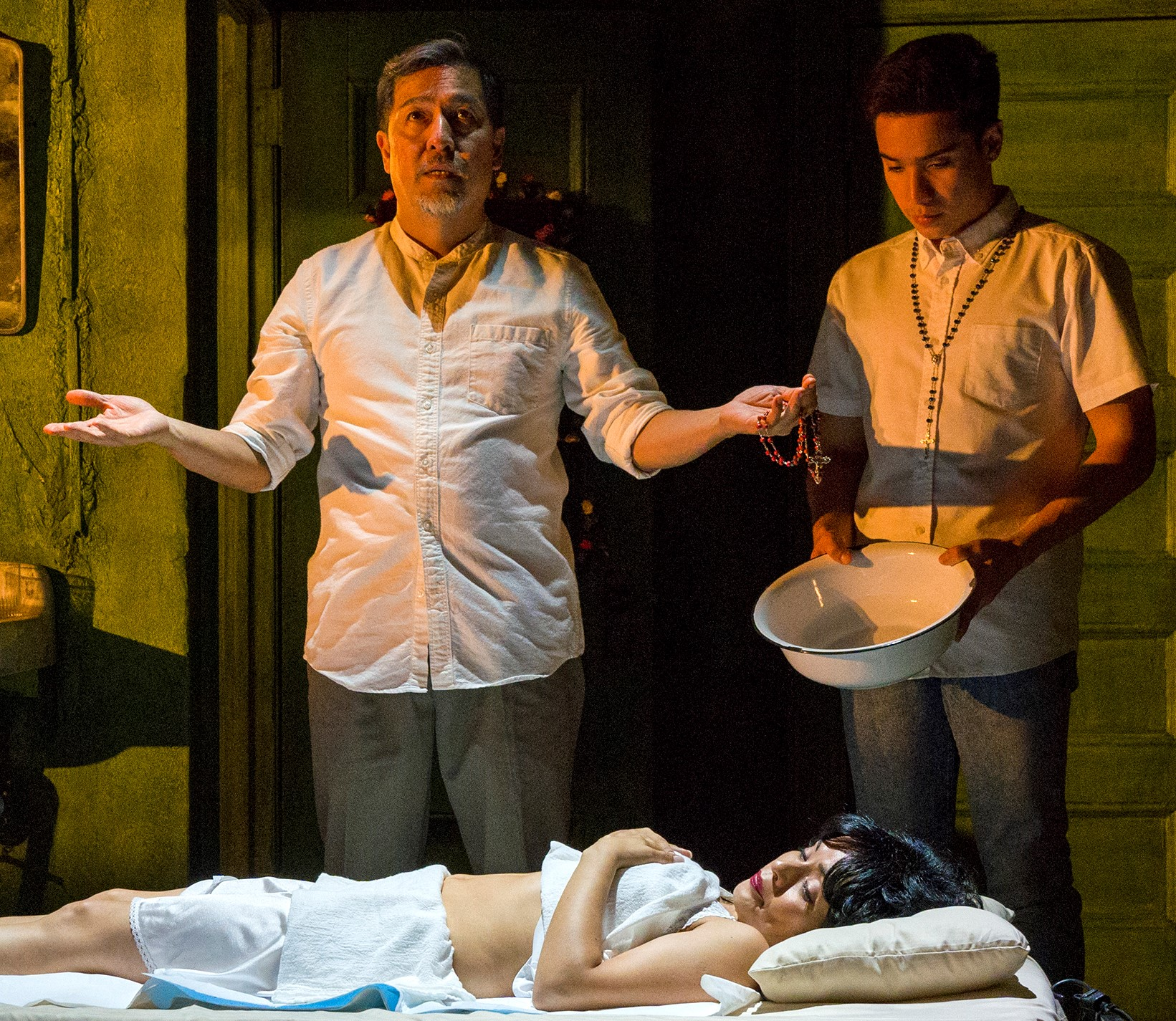 Alan Ariano (left) in the title role of  Felix Starro  and his namesake grandson (Nacho Tambunting), attempt to heal a dying widow (Francisca Muñoz) in the new musical from the Ma-Yi Theater Company.