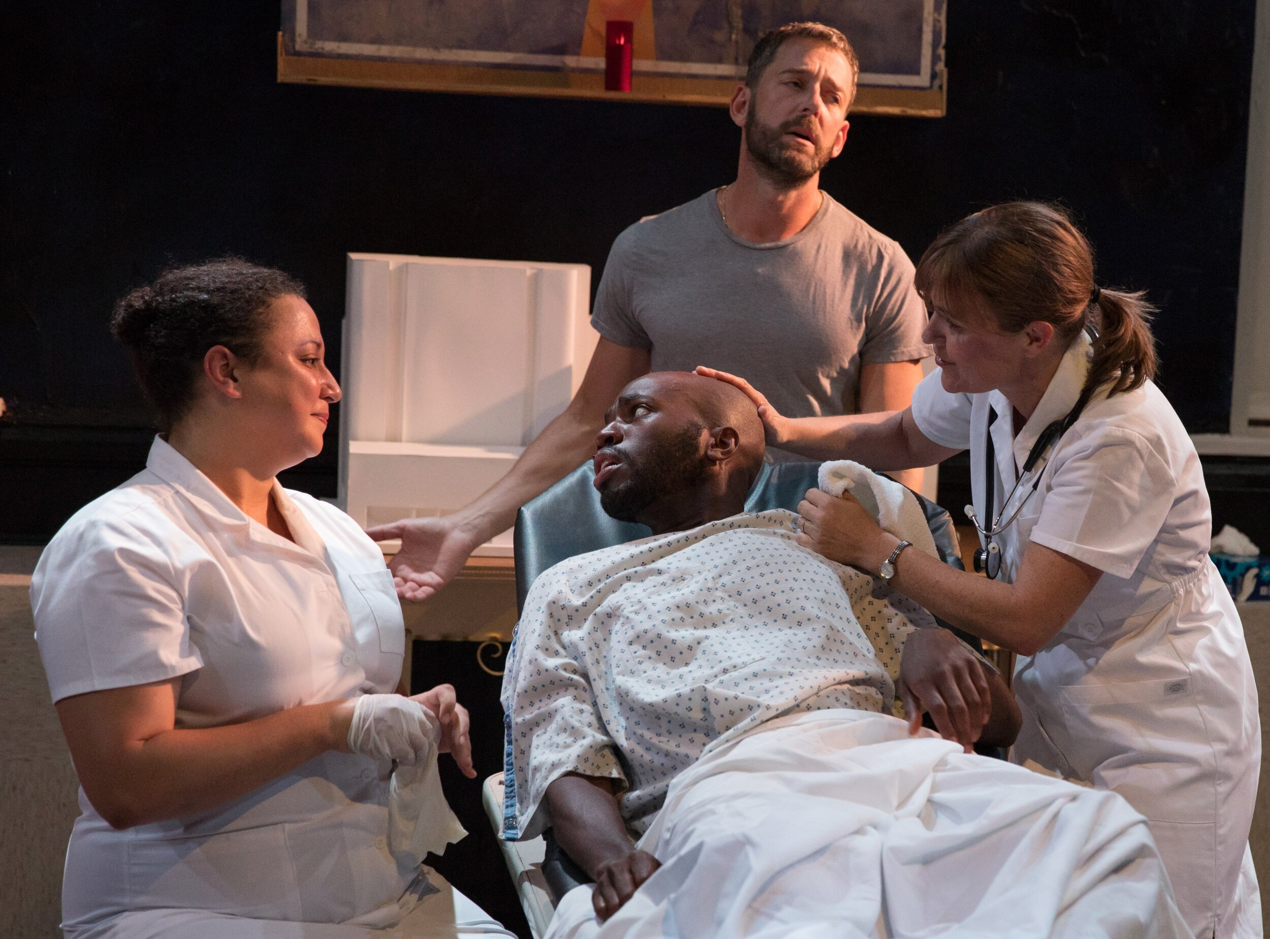 Nurse No. 2 (Natalie Woolams-Torres, left) and Nurse No. 1 (McAndrew) lovingly look on while Lazarus (Ken Barnett, standing) narrates his story with a patient (Leland Fowler). Photographs by Juieta Cervantes.
