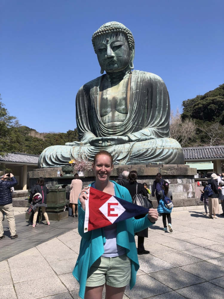 In Tokyo, Japan, Sara Goetze (daughter of Gary & Jane Powell) shows the EYC colors at the feet of the Buddha.