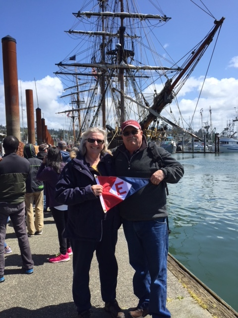 Kathy and Paul Morrow hoist the colors in front of tall ship Lady Washington in Newport, OR.