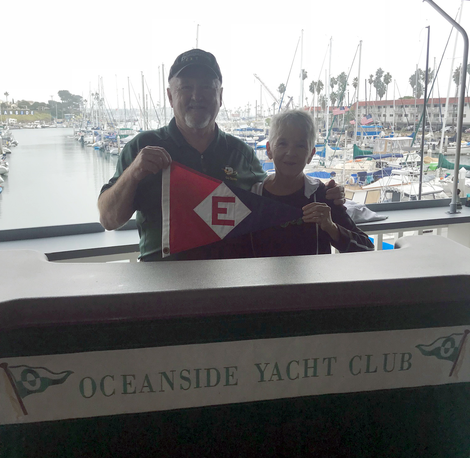 Rex and Bonnie Ballenger hoist the colors at the Oceanside Yacht Club bar.