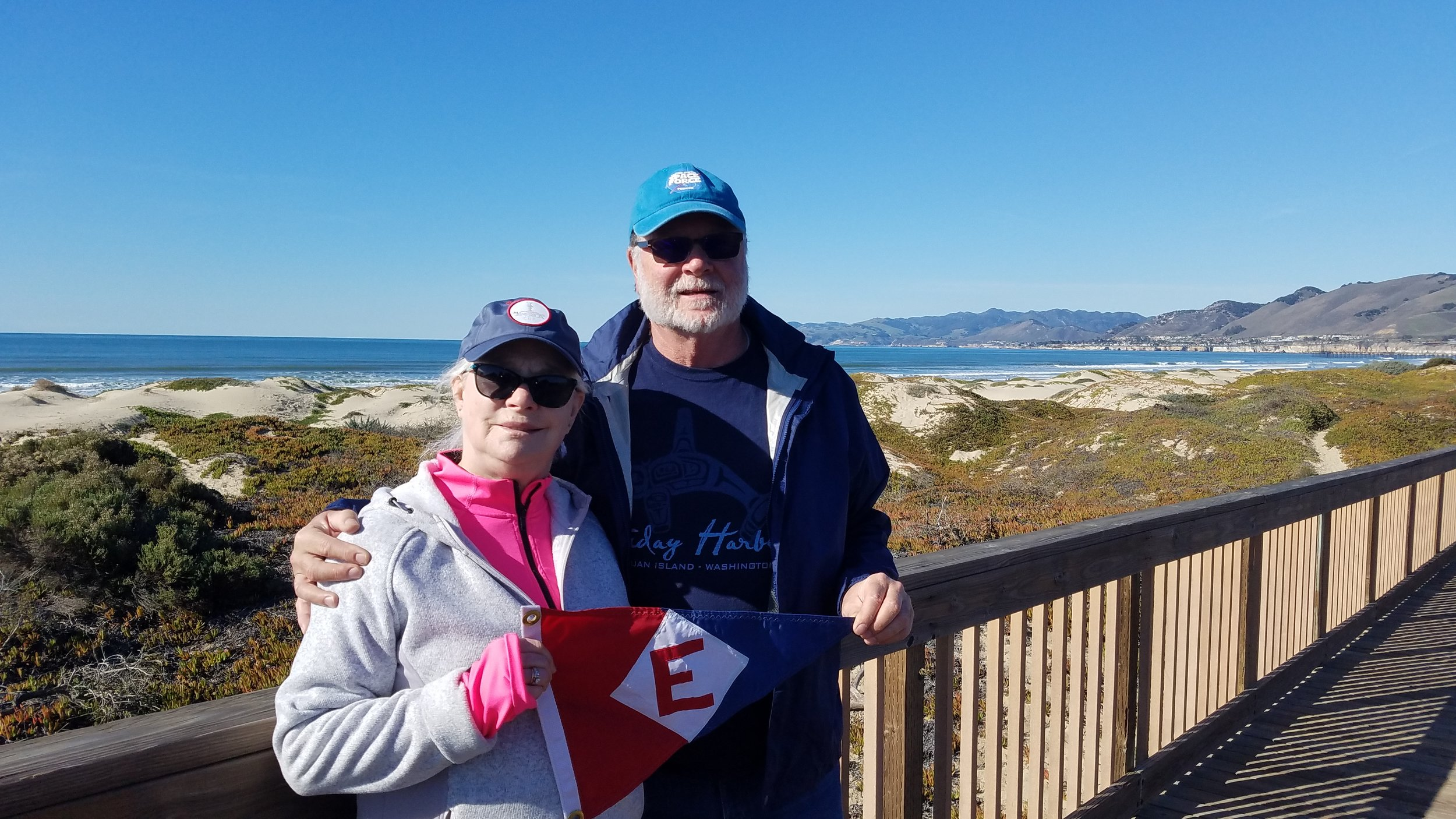 Linda & Murray McLeod hoist the colors in Pismo Beach, California