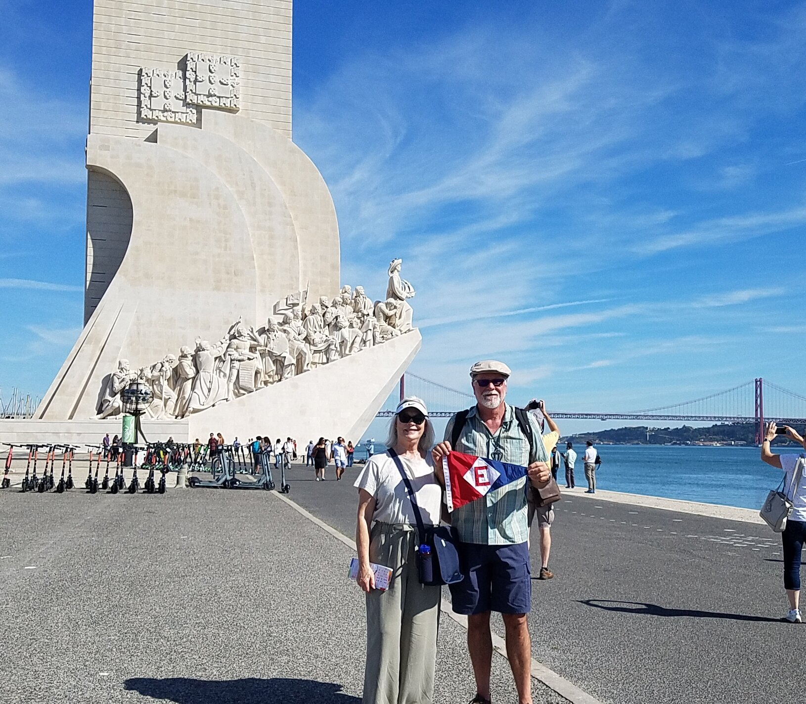 Linda and Murray show the colors in front of the Vasco de Gama Memorial in Lisbon, Portugal