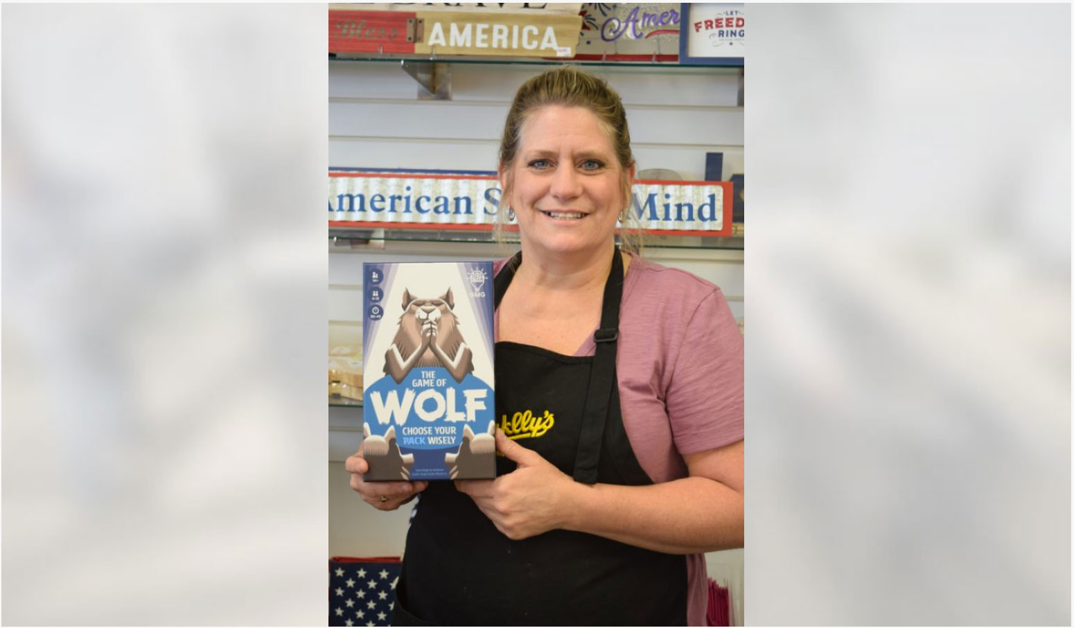 Deborah Prescott | Daily Press Sales associate Chrisy Grandahl holds The Game of Wolf at Sayklly's Confectionary and Gifts on North Lincoln Road Tuesday afternoon. The game is the latest creation from Joe Barron, a 2001 graduate of Escanaba High School. Barron and his wife Lauren created a business called Gray Matters Games. Their goal is to get people away from their cell phones and tablets and interact with other people by playing games while supporting brain health. A portion of proceeds go toward Alzheimer's disease research