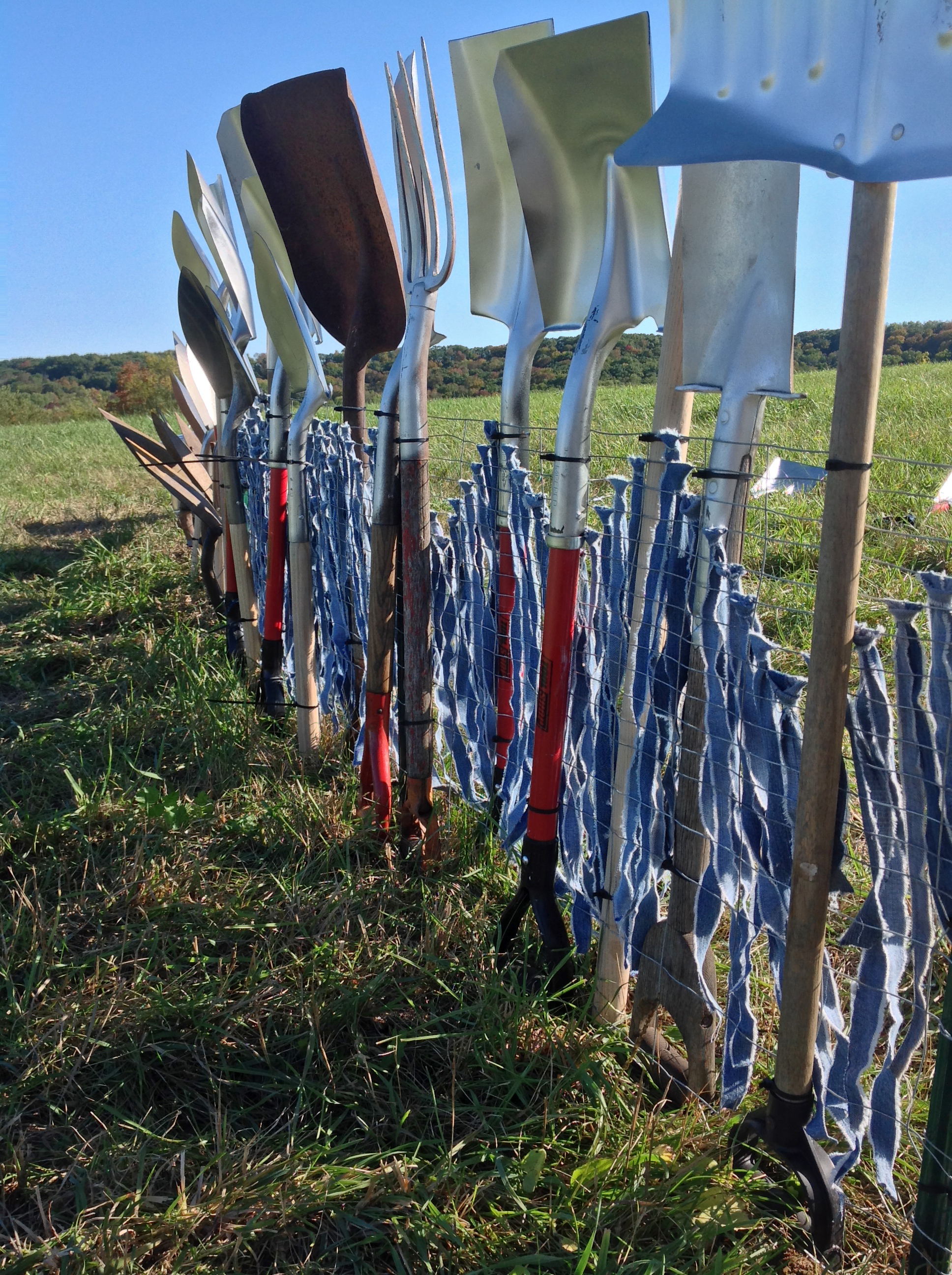 2013  Site specific temporary installation as part of Fermentaion Fest's Farm Art D-tour in Reedsburg, WI.  Approximately 500 shovels to make a 125 foot fence. Denim for tithing was donated, added by viewers.  Photography by author and by Florence Katzenbach