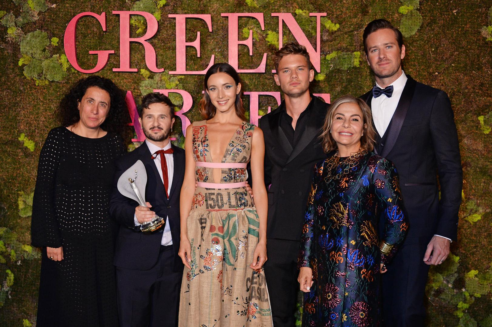 Sara Maino with Franca Sozzani Green Carpet Award for Best Emerging Designer 2018 winner, Gilberto Calzolari. The model wears Calzolari's distinctive gown made from used coffee been sacks. Also pictured Jeremy Irvine, Desirée Bollier, Armie Hammer.