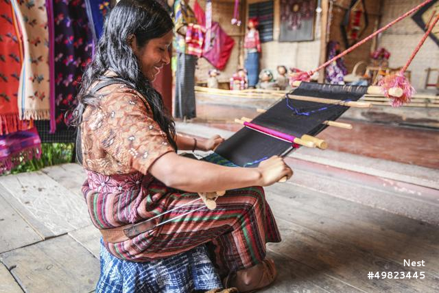 A woman weaves on a backstrap loom in Antigua, Guatemala, a skill she learned from her mother when she was a young teenager. The required tension on the loom is created by a piece of fabric which is held on the hips of the weaver, allowing them to feel physically connected to each throw of the shuttle and movement of the weave. The final panels will be sewn together in pairs and sold in the local market.