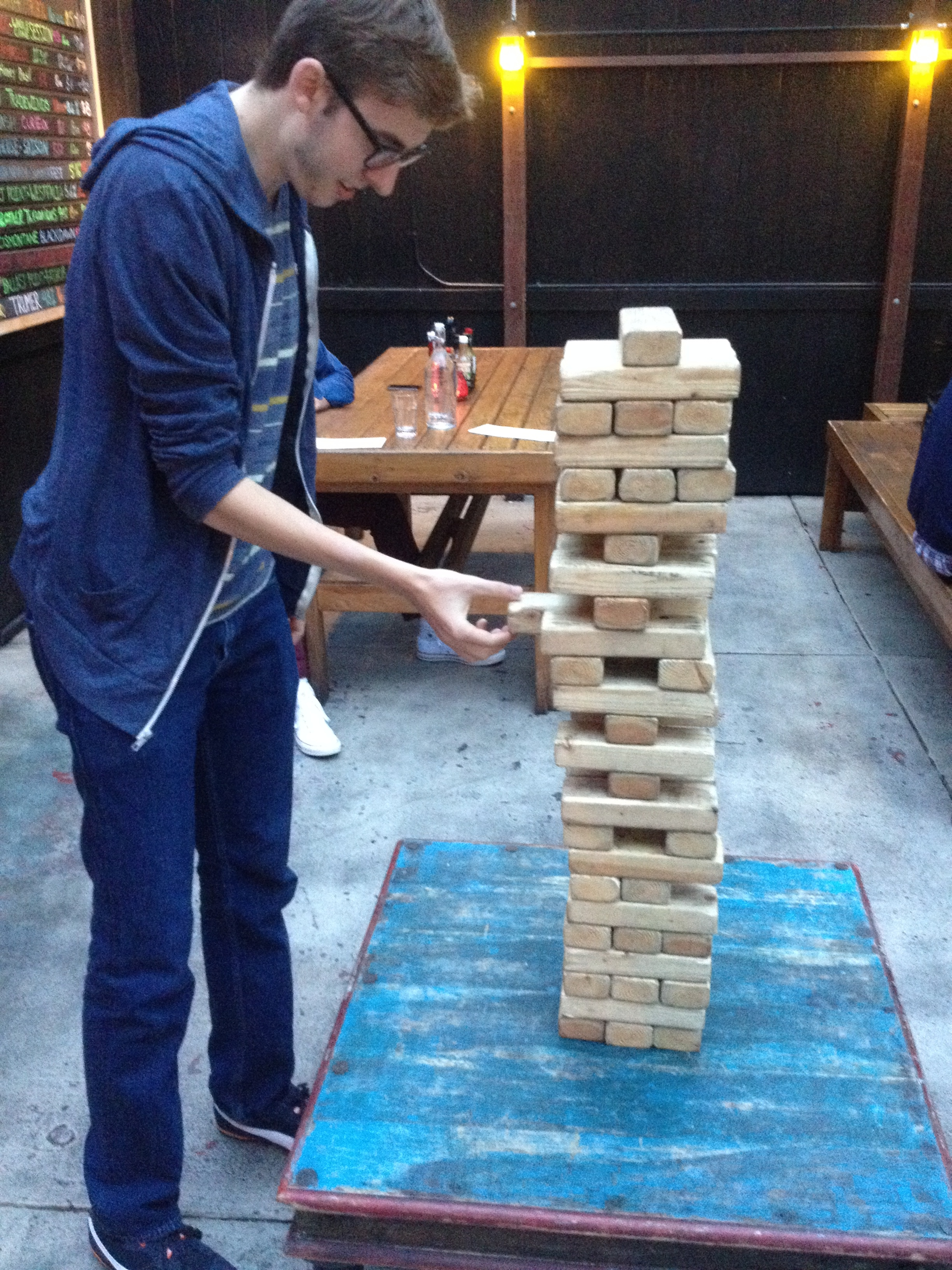 Colin playing a giant Jenga game at a restaurant