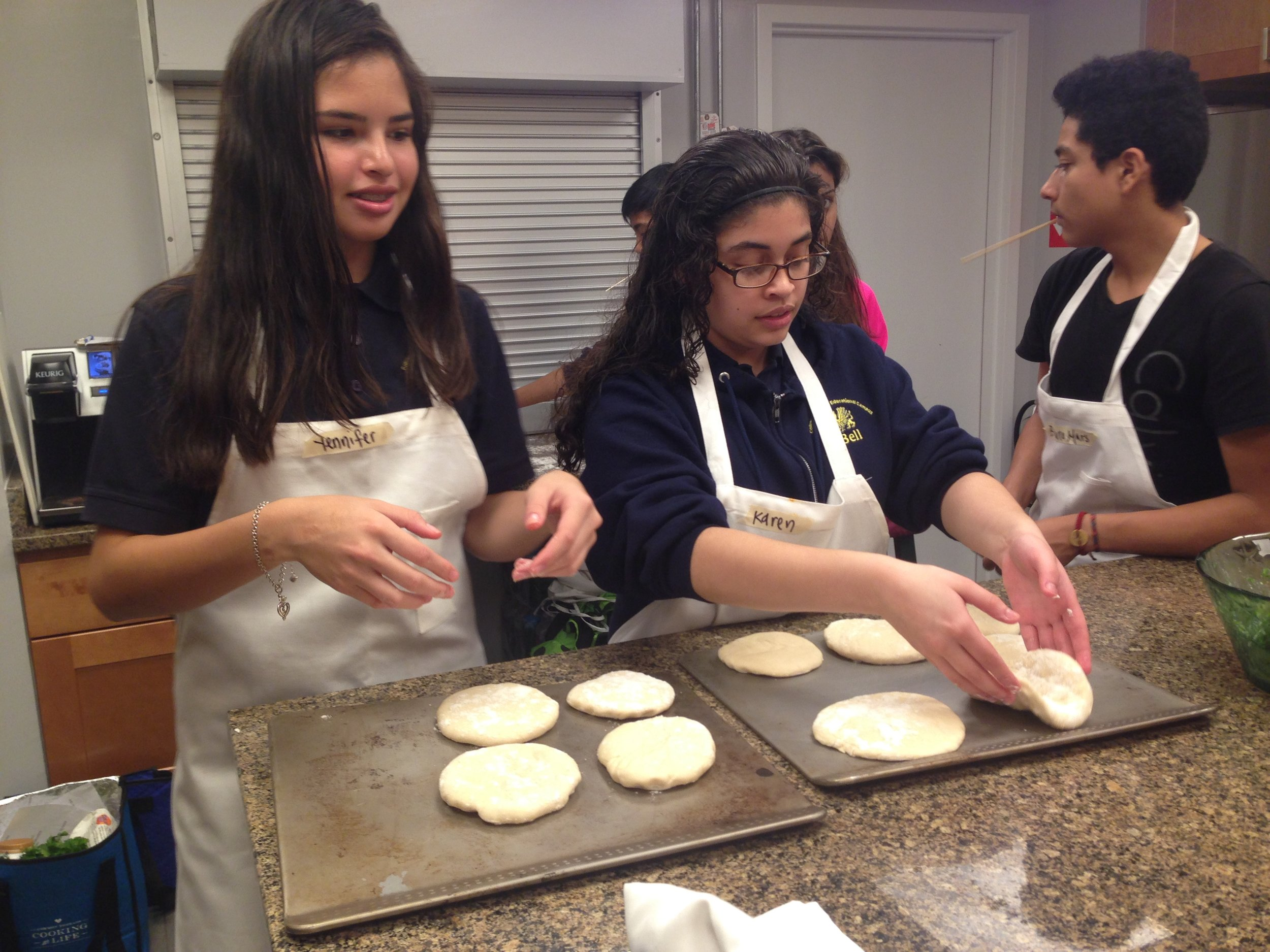 Youth in a cooking class carefully place homemade pita on hot pans to bake