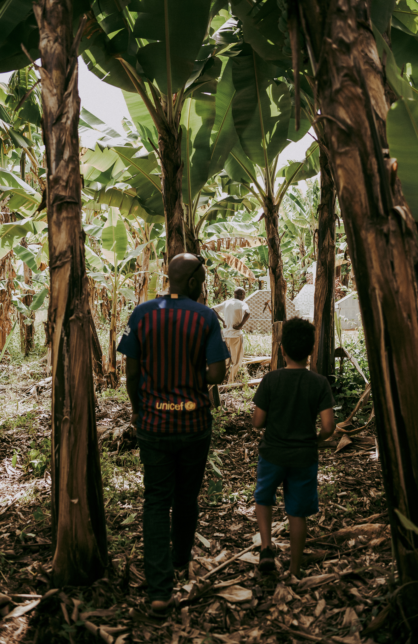 As I was going through the photos, i noted this one particularly. Here is a photo of Mwita and Jordan walking through a dense canopy of banana trees through the property his mom grew up on, to view the graves of his grandparents. You can see the graves in the far right of the photo, Jordans great-grandparents, whom he never met but shares a middle name with. Generations later this is the very spot, the root, half of their heritage.