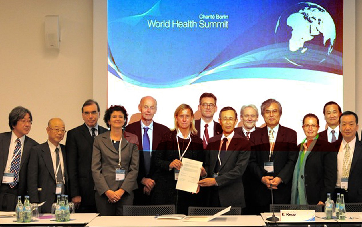 Signature of an official   Cooperation Agreement between the Charité and Juntendo  in 2011 by the Dean of the Charité Prof. Annette Grüters-Kieslich and by the President of Juntendo University Prof. Eiki Kominami during the World Health Summit 2011 in Berlin