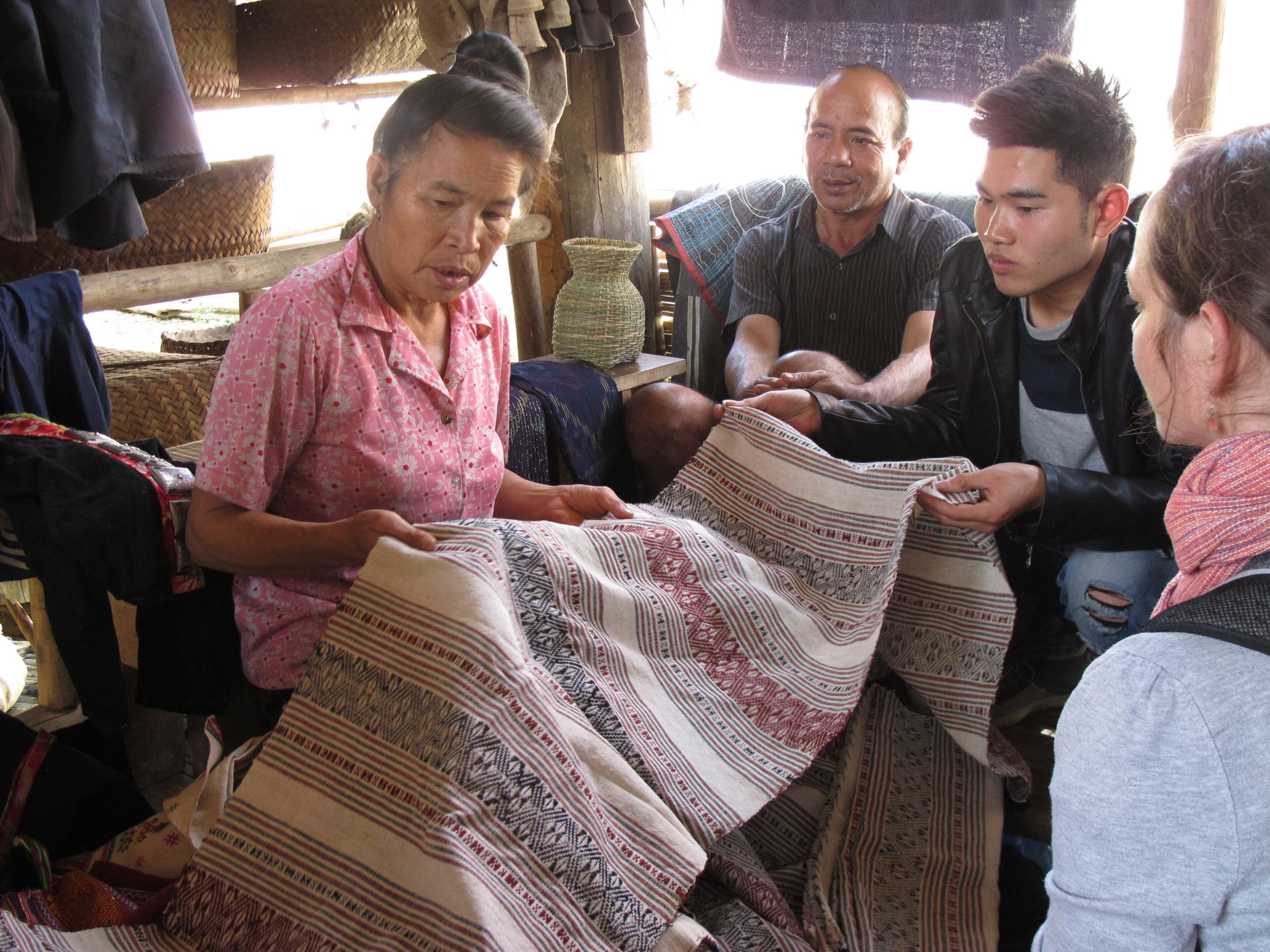 Padee showing us her hand woven textiles, with her husband, Sin, and me looking on