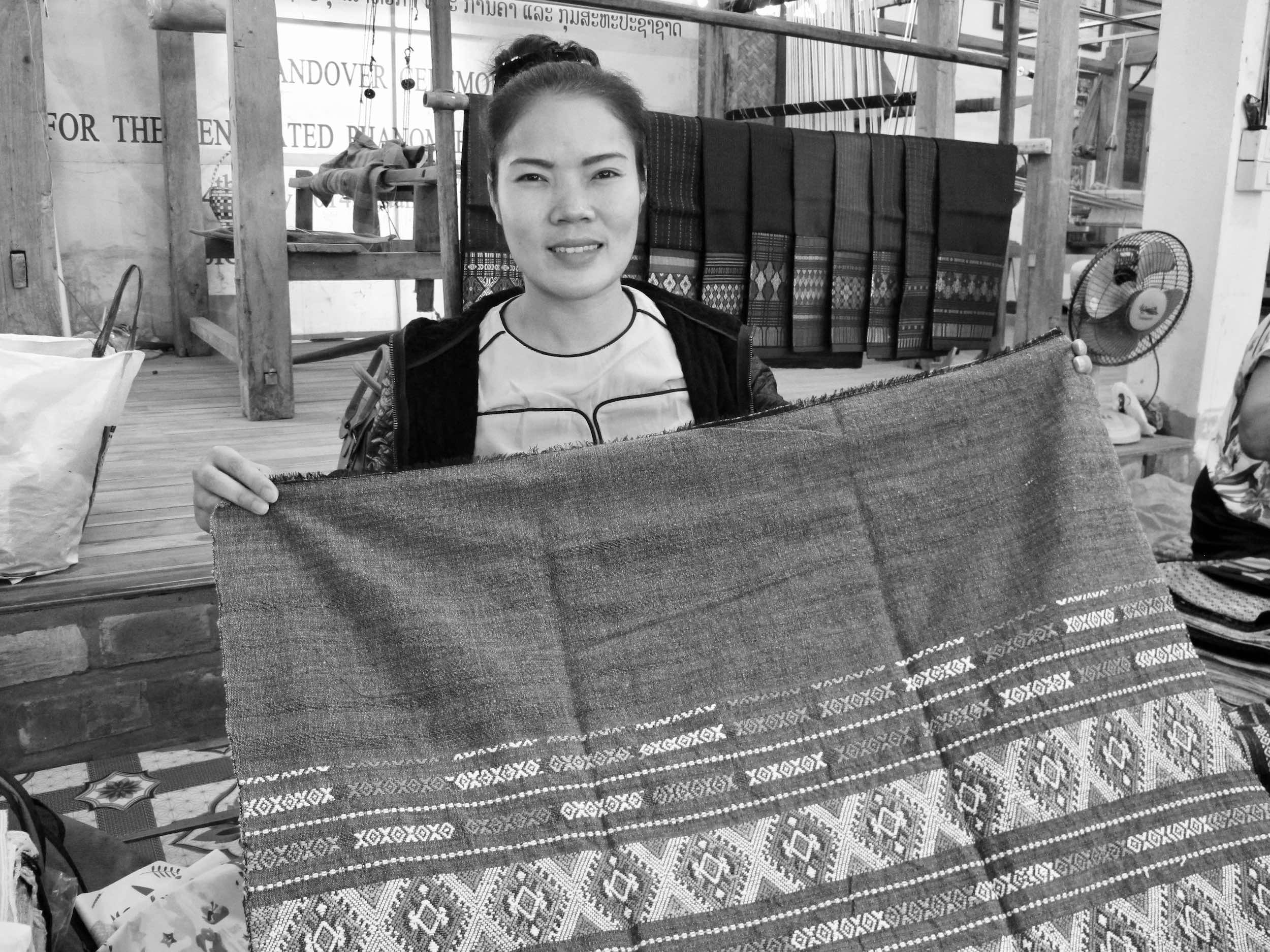 February 2018 – Ban Phanom, Luang Prabang, Laos – Ta is a master Tai Lue weaver. Her fine, well-crafted designs and natural colors are incredible. Here she is with the beautiful diamond crab design in grey green.