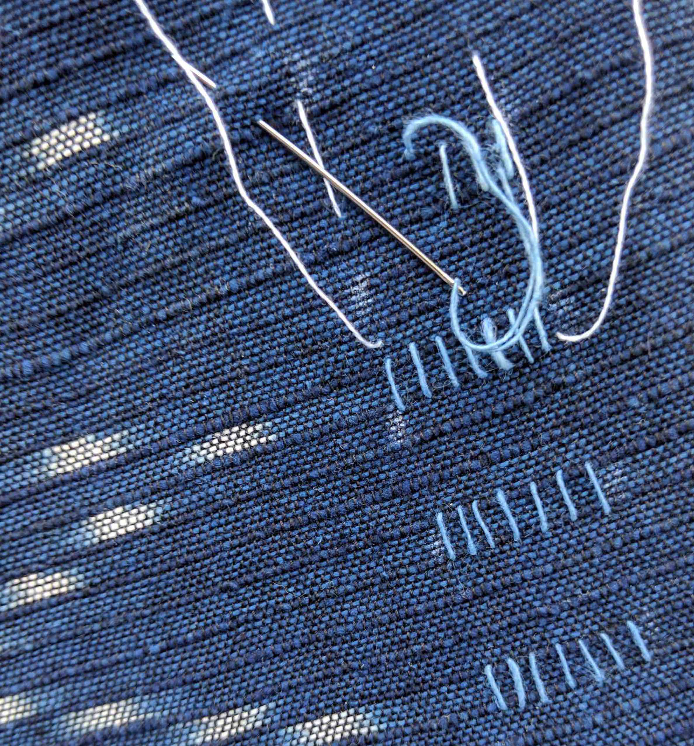 It's somewhat difficult working with this thread, as it tends to break more easily. I go slow. All this takes time. I'm also stitching the pattern in between the indigo ikat fabric and the lining to minimize thread on the inside. But I love the variation of thread's thickness, which adds another visual language to the simple stitches. I decided to use a guide to keep my rows and columns straight, too!