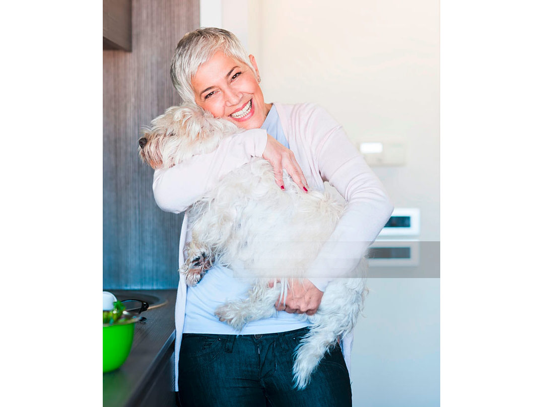 mature-woman-holding-dog-at-home-picture-id636006646.jpg