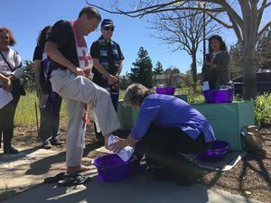 Reverend Wilma Jakobsen of St. Jude's Episcopal church in Cupertino washes the feet of Father Jon Pedigo outside the U.S. Immigration and Customs Enforcement office in Morgan Hill March 29. - By Michael Moore