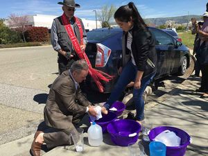 Santa Clara County Supervisor Dave Cortese washes the feet of Delma Hernandez outside the ICE facility in Morgan Hill March 29, with retired priest Jim Leehan of St. Jude's Episcopal church and other clergy members looking on.- By Michael Moore