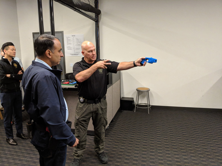 Assemblyman Ash Kalra, D-San Jose, left, listens as San Jose police Officer Theodore Davis, right, instructs him during a session with the department's force-option simulator at the SJPD substation in South San Jose on Aug. 17, 2018. (Robert Salonga/Bay Area News Group)