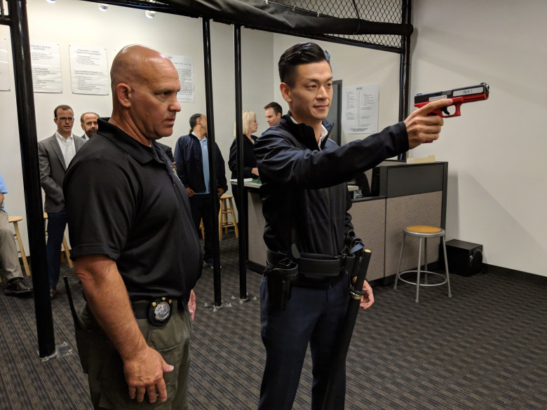San Jose police Officer Theodore Davis, left, instructs Assemblyman Evan Low, D-Campbell, during a session with the department's force-option simulator at the SJPD substation in South San Jose on Aug. 17, 2018. (Robert Salonga/Bay Area News Group)