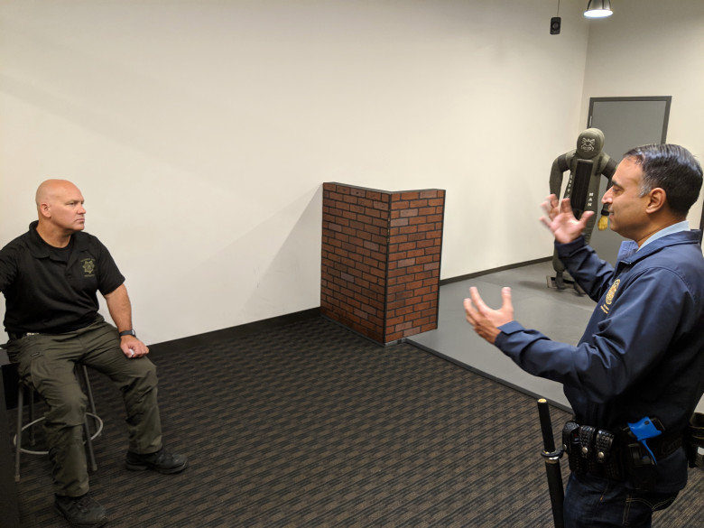 Assemblyman Ash Kalra, D-San Jose, right, is debriefed by San Jose police Officer Theodore Davis, left, during a session with the department's force-option simulator at the SJPD substation in South San Jose on Aug. 17, 2018. (Robert Salonga/Bay Area News Group)