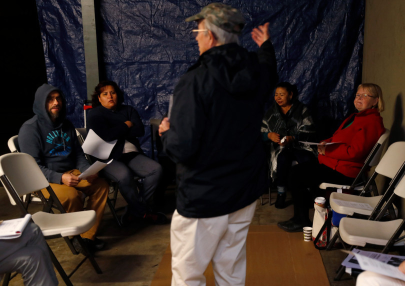 Mountain View, CA - DECEMBER 3: Philip Cosby, a parishioner with Saint Athanasius Church, leads a meeting of residents in a carport at their rent controlled apartment building along Rock St. in Mountain View, Calif., on Monday, Dec. 3, 2018. They meet every week. Mountain View city officials are considering a developer's proposal to raze 20 rent-controlled, affordable apartments and replace them with 15 new, luxury town houses. (Nhat V. Meyer/Bay Area News Group)
