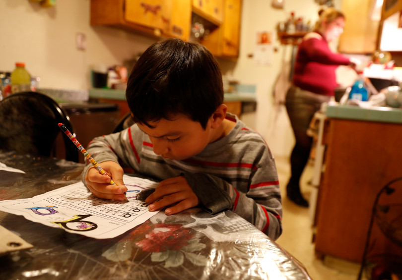 Mountain View, CA - DECEMBER 4: Johnatan Flores Carrillo, 5, works on his kindergarten homework as his mother Rocio Carrillo prepares dinner in their apartment on W. Middlefield Rd. in Mountain View, Calif., on Tuesday, Dec. 4, 2018. Mountain View city officials are considering a developer's proposal to raze 20 rent-controlled, affordable apartments and replace them with 15 new, luxury town houses. (Nhat V. Meyer/Bay Area News Group)