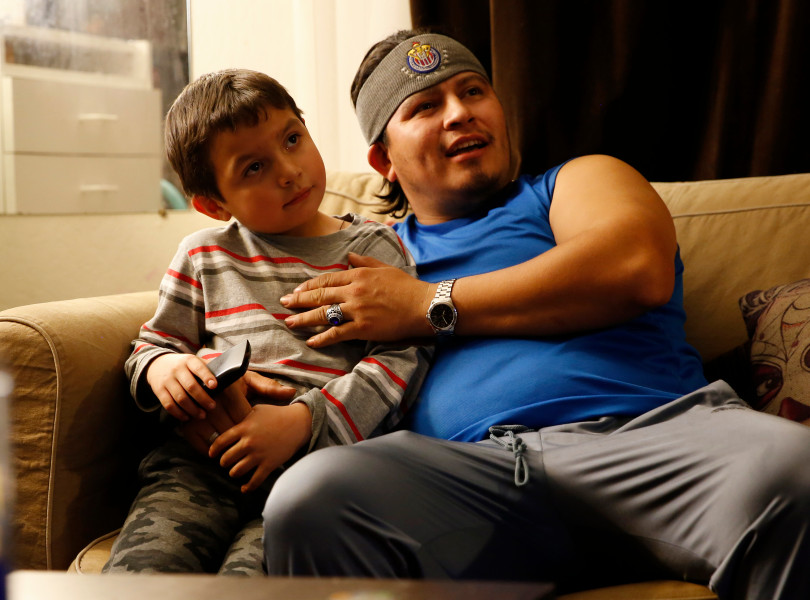 Mountain View, CA - DECEMBER 4: Johnatan Flores Carrillo, 5, watches television with his dad Roberto Flores in their apartment on W. Middlefield Rd. in Mountain View, Calif., on Tuesday, Dec. 4, 2018. Mountain View city officials are considering a developer's proposal to raze 20 rent-controlled, affordable apartments and replace them with 15 new, luxury town houses. (Nhat V. Meyer/Bay Area News Group)