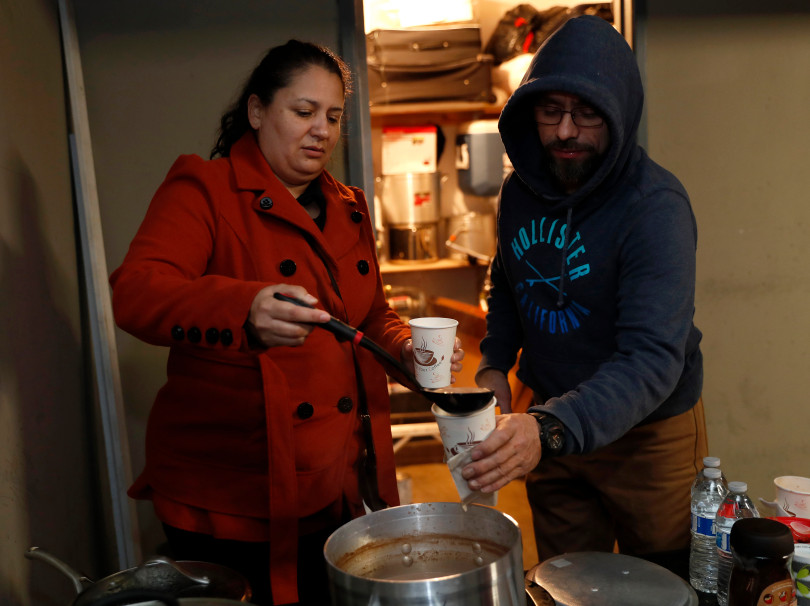 Mountain View, CA - DECEMBER 3: Resident Guadalupe Rosas, left, pours Donis Morales some hot chocolate during their meeting in a carport at their rent controlled apartment building along Rock St. in Mountain View, Calif., on Monday, Dec. 3, 2018. They meet every week. Mountain View city officials are considering a developer's proposal to raze 20 rent-controlled, affordable apartments and replace them with 15 new, luxury town houses. (Nhat V. Meyer/Bay Area News Group)