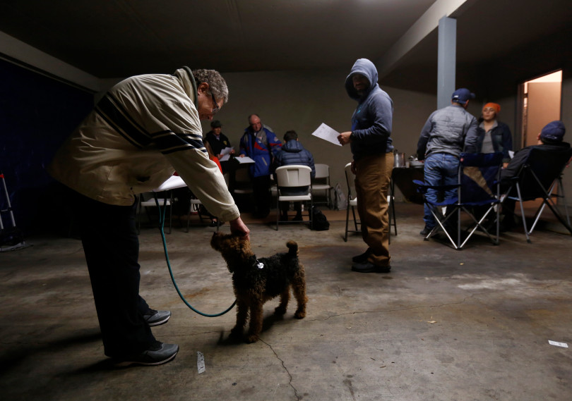 Mountain View, CA - DECEMBER 3: Neighbor Dave Arnone pets his dog Cali, a 3-year-old Welsh Terrier, before a meeting in a carport at the rent controlled apartment building along Rock St. in Mountain View, Calif., on Monday, Dec. 3, 2018. Arnone lives in a home down the street but attends meetings in support. Residents meet every week. Mountain View city officials are considering a developer's proposal to raze 20 rent-controlled, affordable apartments and replace them with 15 new, luxury town houses. (Nhat V. Meyer/Bay Area News Group)